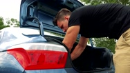 Young handsome man puts straight load in car trunk  Stock Footage