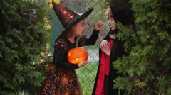Children wearing witch costumes with hats playing with pumpkin with a burning Stock Footage