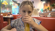 The girl is drinking juice in a cafe Stock Footage