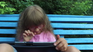 Girl child in glasses enthusiastically working on a tablet computer. Stock Footage