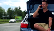 Young handsome man sits in car trunk and phones with smartphone - road with cars Stock Footage