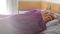 Elder couple sleeping in bed with light rays coming from open window Stock Footage