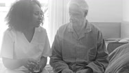 Monochromatic scene with senior man swallowing pills prescripted by nurse Stock Footage