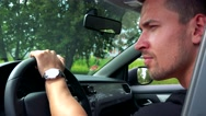 Young handsome man looks around behind the wheel in the car - nature  Stock Footage