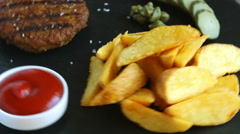 Grilled burger with potatoes and pickled cucumber sauce Stock Footage