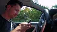 Young handsome man drives a car (wait) and typing on smartphone - nature Stock Footage