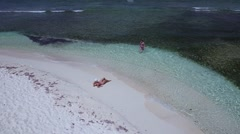 Aerial view of women relaxing on the beach, Lindquist beach, St Thomas Stock Footage