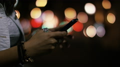 Hands using a phone in the city at night with blurred background lights  Stock Footage