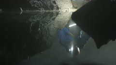 4K Geologist exploring underground cave, looking at rock formation & water pool Stock Footage