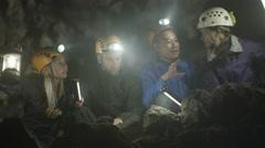 4K Portrait smiling spelunkers exploring underground cave Stock Footage