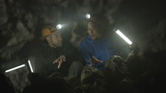 4K Spelunkers exploring underground cave, discussing rock formation Stock Footage