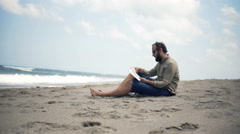 Young man reading book sitting on beach near sea Stock Footage