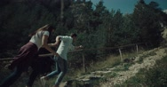 A couple run hold hands towards a forest. Stock Footage