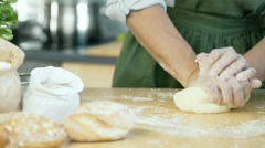 View of woman hands kneading the dough on the wooden table, dolly shot Stock Footage