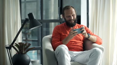 Young man playing game on smartphone sitting on armchair at home Stock Footage