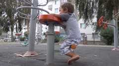 Kid has fun whirling on exercise machine  Stock Footage