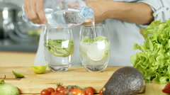 Woman pouring water to the glasses and making refreshing drink, dolly shot Stock Footage