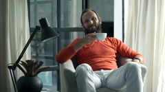 Portrait of happy man drinking coffee on armchair at home Stock Footage