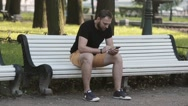 Attractive young man sitting on a bench in the park and using a smartphone sends Stock Footage