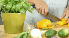 Woman cutting yellow papper on the woode board and throw it into bowl, dolly sho Stock Footage