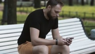 Close-up attractive young man sitting on a bench in the park and using a Stock Footage