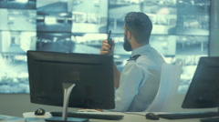 4K Security officer watching the screens & talking on radio in control room Stock Footage