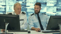 4K Security officers watching the screens & talking on radio in control room Stock Footage