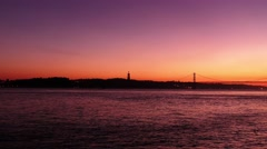 Zoom-in: Sunset view of Christ the King Statue and 25th of April Bridge, Lisbon Stock Footage