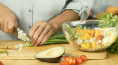 Woman chopping chives on the wooden board in the kitchen, dolly shot Stock Footage