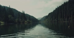 Amazing landscape of mountain lake and tall trees. Water ripples on lake. Stock Footage