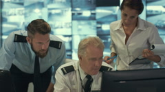 4K Security staff watching screens & discussing in observation control room Stock Footage