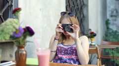 Happy girl doing photos on old, vintage camera in the outdoor cafe Stock Footage