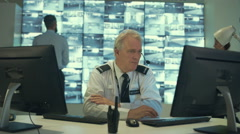 4K Security officer communicating via headset in control room Stock Footage