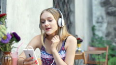 Happy girl listening music on headphones and singing in the outdoor cafe Stock Footage