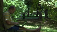 Shabby man working with laptop computer sitting under old tree in park. 4K Stock Footage