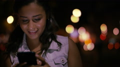 Attractive young woman using her phone in the city at night, with space for tex Stock Footage