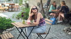 Stylish girl wearing sunglasses and sitting by the wooden table in outdoor cafe Stock Footage