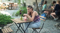 Worried girl looking thoughtful while sitting by the wooden table  Stock Footage