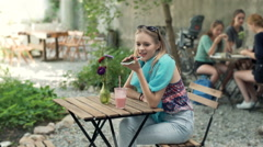 Girl in blue scarf sitting by the wooden table and talking on loudspeaker Stock Footage