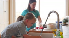 Mother and boys chop tomatos for fresh salsa Stock Footage