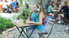Happy girl listening music on headphones while sitting in the outdoor cafe Stock Footage