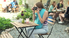 Girl doing photos on old camera in the outdoor cafe, steadycam shot Stock Footage