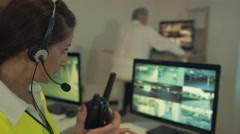 4K Security team watching CCTV video screens in observation control room Stock Footage