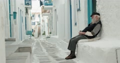 Old man sits on a narrow street in white on the island of Mykonos Stock Footage