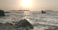 Two ships sailing at sunset near island Stock Footage