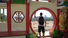 Caucasian man enjoy panorama city view from round doorway of Chinese temple Stock Footage