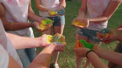 Multinational group of young people holding a lot of colored paint Holi in the Stock Footage