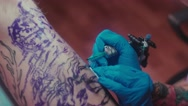 Tattoo machine in the hands of the master. Large tattoo pattern Stock Footage