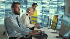 4K Stressed out security guard working with colleagues in control room Stock Footage