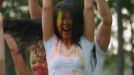 Group of young friends in the Park with the colors of Holi, dancing and having Stock Footage